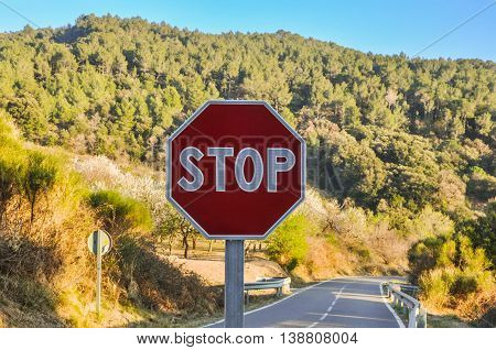 Octagonal stop sign in the background of beautiful forested mountainous landscape and road. Horizontal.