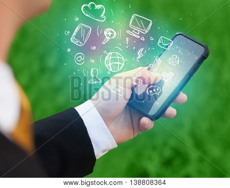 Hand holding smartphone with glowing multimedia icons