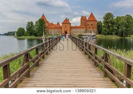 TRAKAI, LITHUANIA - JUNE 22, 2013: Bridge leading to the red brick castl in Trakai, Lithuania