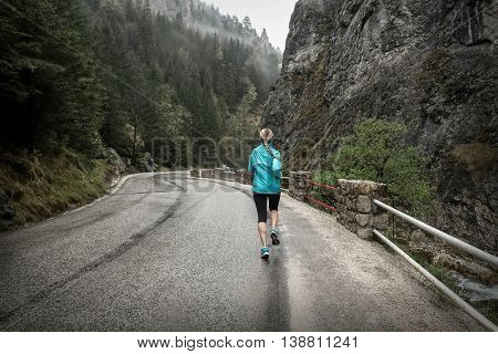Running on the road around mountains under snowly rain.