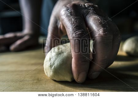 Hands kneading the dough on a wooden table