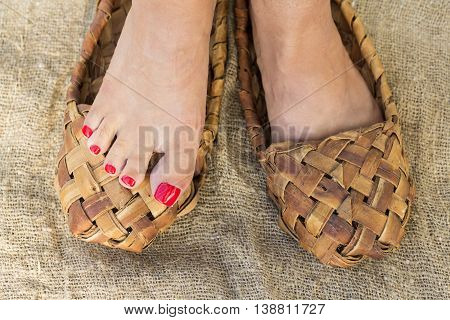 Feet girls with trendy pedicure in bast shoes stand on canvas.