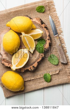 Slices half fresh juicy lemon with mint leaves and knife on the vintage wooden table. Top view with copy space.