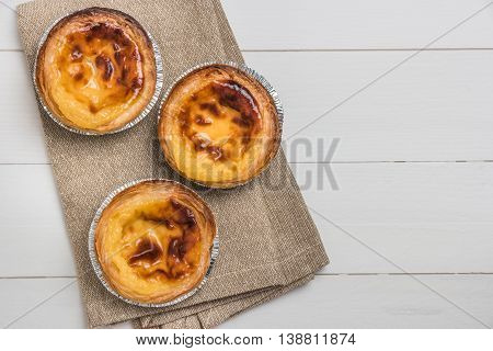 Pasteis de nata typical Portuguese egg tart pastries on a set table. Top view with copy space