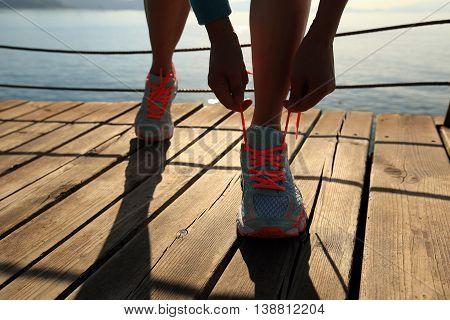 sports woman tying shoelace on wooden boardwalk sunrise seaside
