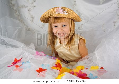 A young blue eyed girl smiles for a portrait. She is dressed in a gold hat and dress that match her golden hair. There is tulle in front of her with fake flower petals sprinkled in and a fancy white backdrop behinde her.