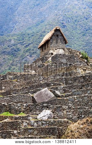 old house in Machu Picchu mountains in the background