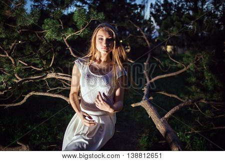 Girl in a white dress in the fairy forest. Mystery night