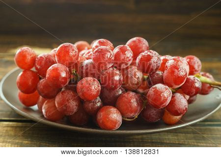 Bunch of red grapes on a plated on dark background