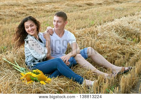 happy young couple sit in wheaten field at evening, romantic people concept, beautiful landscape, summer season