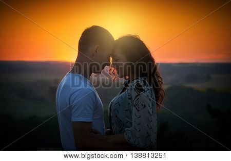 young couple at sunset on sky background, love concept, romantic people