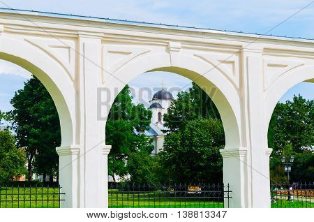 Architecture landscape with old arcade of the ancient Yaroslav courtyard at summer sunny day in Veliky Novgorod Russia - unusual composition with the St Nicholas Cathedral in one of the arches.