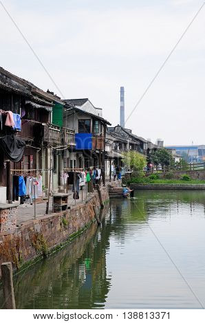 Chinese style homes and dyring laundry lining the side of the water canals of Xinshi Town in Zhejiang Province of China.