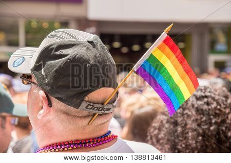 Toronto Canada - July 3 2016: A male spectator is watching the gay pride parade with a gay rainbow flag attached to his cap