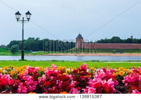 Architecture landscape of Novgorod Kremlin and water area of Volkhov river with flowerbed on the foreground in summer cloudy day Veliky Novgorod Russia. Selective focus at the architecture.