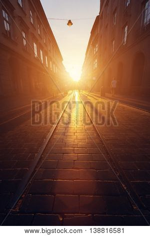 Empty cobblestone street in old town at sunset. Warm direct sunlight