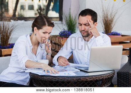 Male and female business colleagues working together on a hard problem. They have a strained expression on their faces