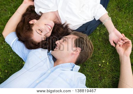 Young couple looking at each other while lying down on the grass
