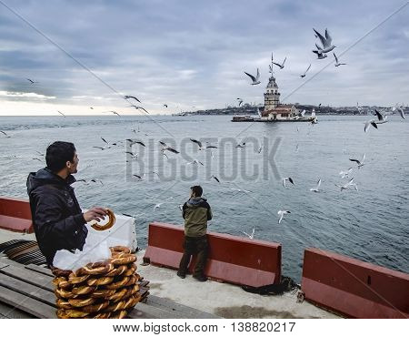 Istanbul Turkey - December 04 2013: A pretzel vendor and a man feeding seagulls appear. European part of Istanbul in the background against the shore. Left Blue Mosque medium Hagia Sophia Topkapi palace dome seem right. The Maiden's Tower (Turkish: Kiz Ku