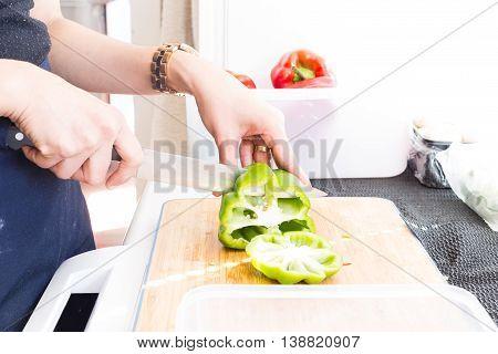 Cutting green bell pepper. also prepare red bell pepper