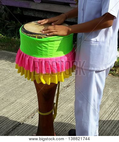 Thai student dressed in white Buddhist ceremonial clothes seen playing decorated traditional klong yao skin and wooden drum, with green, pink, and yellow cloth fringes. Songkhla, Thailand