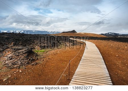 Geothermal area Leirhnjukur. Area Krafla volcano, Iceland, Europe. Tourist trail with wooden planks and fence. Summer landscape a cloudy day