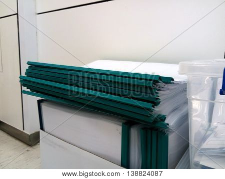 Many Green document folders in the box on the floor
