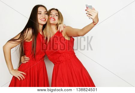 two women wearing red dress taking selfie