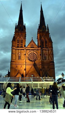 Sydney Australia - July 17 2016. People ice skating on the Winter Festival at St. Mary's Cathedral. The Winter Festival in Sydney is Australia's largest winter events featuring open-air ice-skating.
