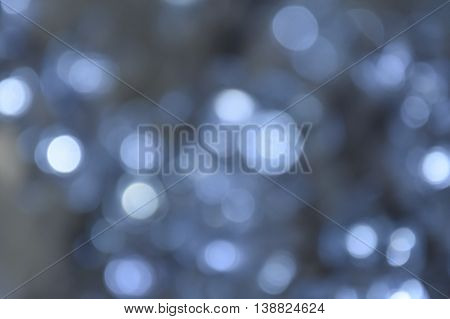 Defocused Bokeh twinkling lights background. Festive background with natural bokeh and bright white and silver defocused lights.