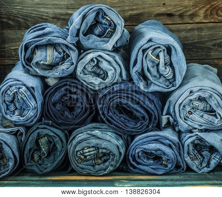 Bunch Of Jeans Twisted On A Wooden Background, Fashionable Clothes