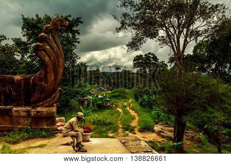 A soldier under an ancient Khmer naga statue watches a small village in Cambodia