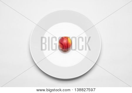 Healthy Eating In The Restaurant And Diet Topic: Beautiful Ripe Nectarine On A White Plate Lies On A