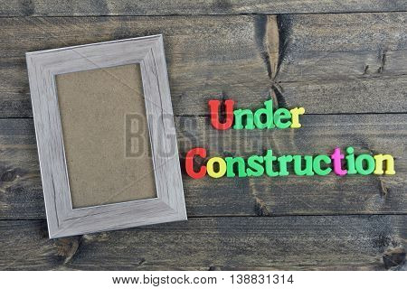 Under Construction word on wooden table