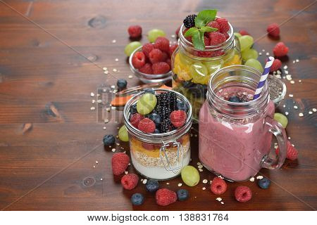 Muesli and smoothies with berries on wooden background