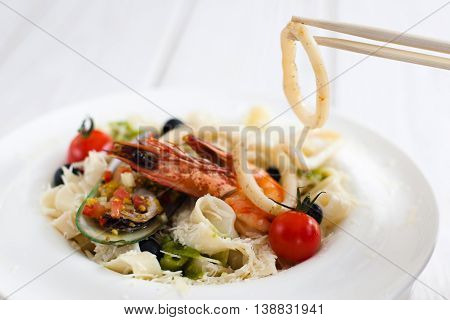 Seafood eating with chopsticks, closeup. Squid ring taking with asian cutlery from plate with seafood mix meal