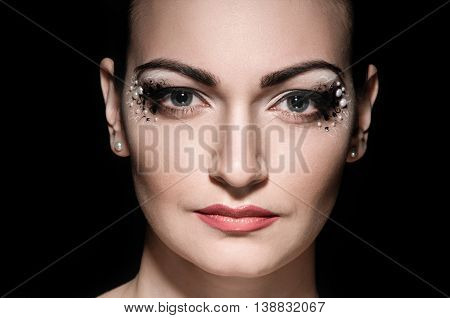 professional make-up and hairstyle on beautiful woman face on black background
