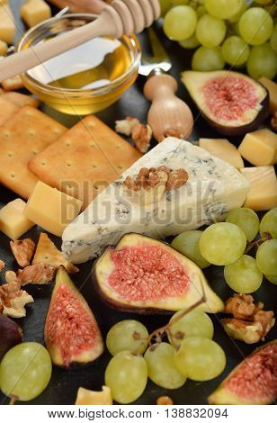 Blue cheese with grapes figs and honey on black background