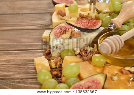 Cheese with grapes figs and honey on wooden background