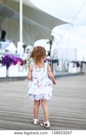 kid walk child walking summer nature childre back dress hair sandals footwear flowers the background