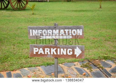 Information and Parking sign, brown wooden green grass background