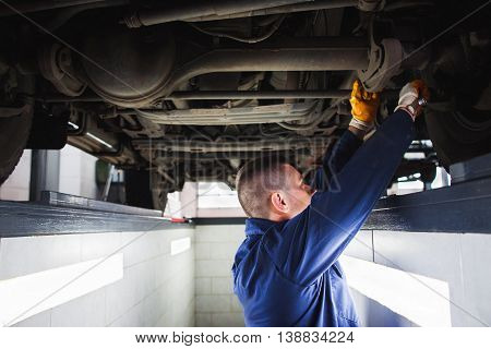 Suspension system of SUV restoration in garage. Mechanic recovering car wheel under vehicle