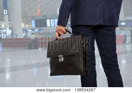 Business trip. Businessman with a briefcase in airport