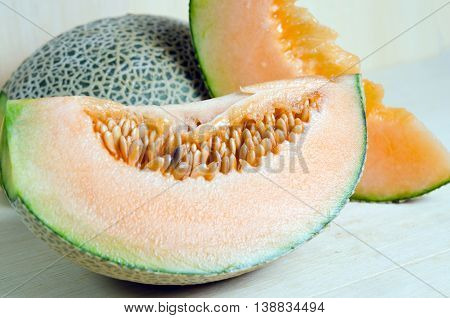Sliced melon with seed on wooden board (Other names are cantelope cantaloup honeydew Crenshaw casaba Persian melon and Santa Claus or Christmas melon)