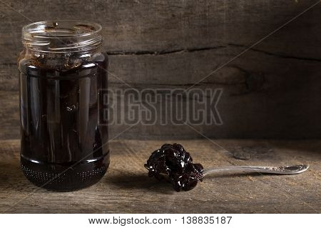 Cherry jam in a preserving glass and spoon over old wooden rustic background