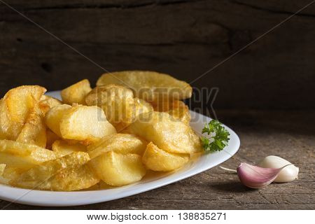 Portion of homemade french fries (potatoes) on white plate and wooden rustic background