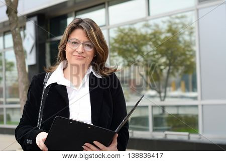 Portrait of business woman holding clipboard standing outdoors.