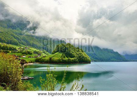 Beautiful emerald mountain lake Lungern in Switzerland under low clouds