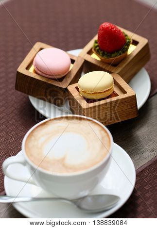 Cup of cappuccino and macaroons in outdoor cafe, selective focus