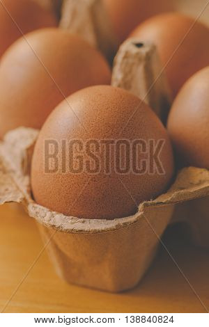 Chicken ginger eggs in cardboard box retro toned selective focus